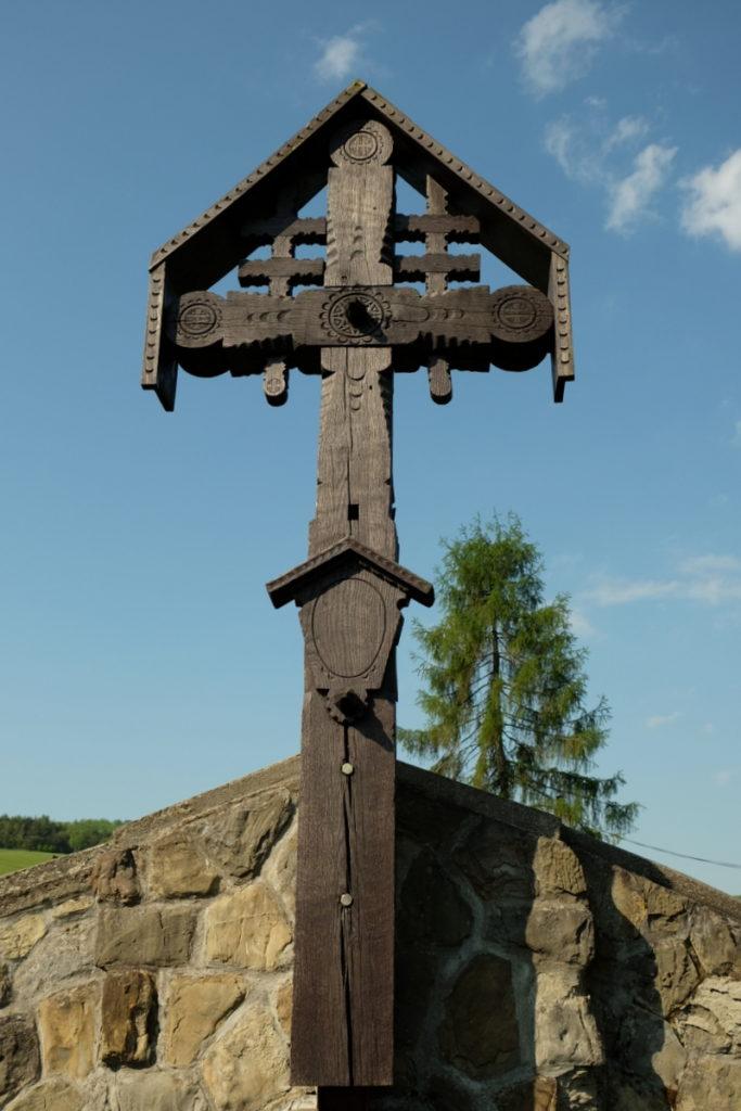 Oryginalny drewniany krzyż wieńczący kamienny mur